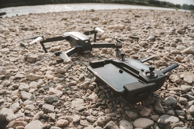 Strzał z bliska zaawansowanego technicznie drona i jego zdalnego urządzenia sterującego na szarych kamykach