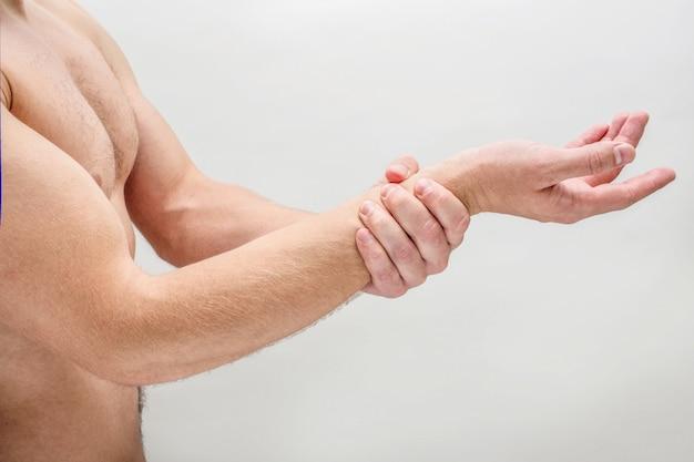 Strzał z boku młodego człowieka trzyma rękę na nadgarstku