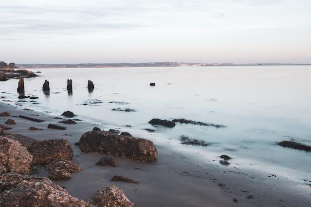 Strzał z długiej ekspozycji kamieni na brzegu w pobliżu portland, weymouth, dorset, wielka brytania