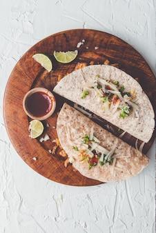 Strzał z góry gotowane pikantne naleśnikowe jedzenie na drewnianym talerzu podawane z keczupem i limonką