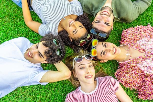 Strzał z góry z pięciu szczęśliwych wielorasowych przyjaciół leżących łeb w łeb z kolorowymi okularami przeciwsłonecznymi patrząc na kamerę od dołu. mieszana grupa rasowa uśmiechniętych uroczych młodych ludzi bawiących się razem na łonie natury