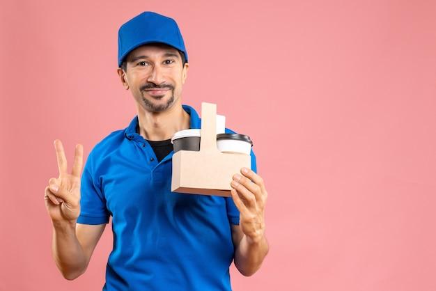 Strzał z połowy ciała uśmiechniętego mężczyzny-dostawcy w kapeluszu, trzymającego zamówienia i karty bankowej, wykonującego gest zwycięstwa