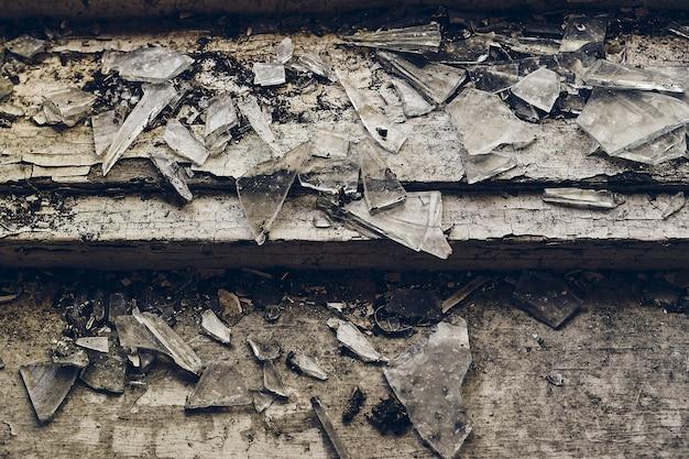 Strzał z rozbitego szkła pod dużym kątem rozrzucony po starych drewnianych schodach