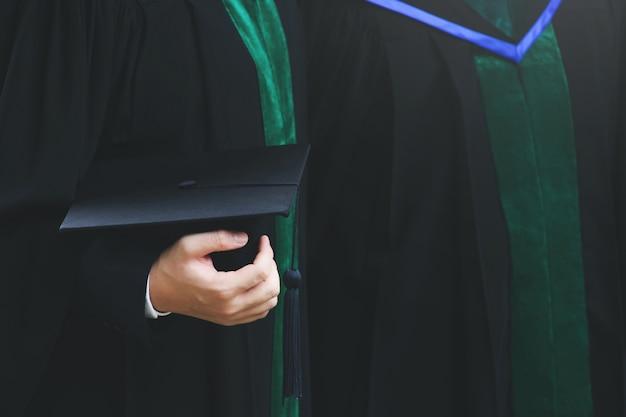 Strzał z tyłu młoda studentka w ręku trzyma bukiet kwiatów absolwentów