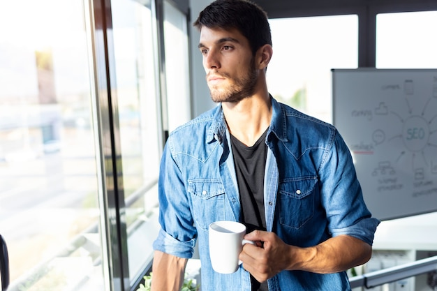 Strzał zamyślony młody biznesmen patrząc przez okno podczas picia kawy i przerwy w biurze.