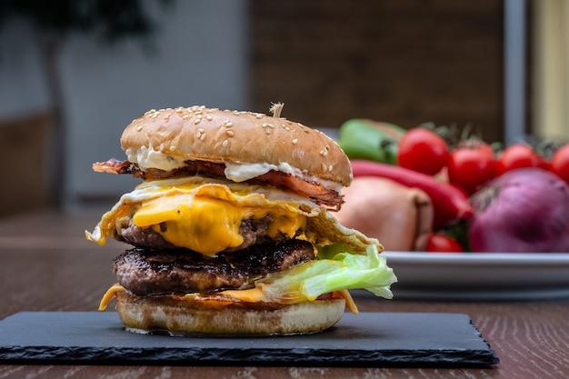 Strzał zbliżenie apetyczny burger na niewyraźne tło