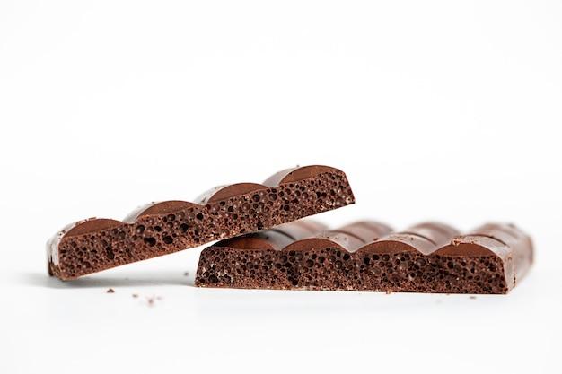 Strzał zbliżenie bąbelków kawałków czekolady na białym tle na białej powierzchni