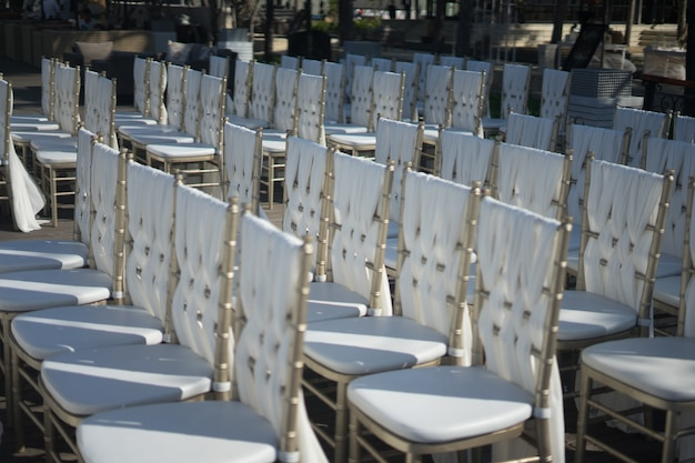 Strzał zbliżenie białe krzesła dla gości ceremonii ślubnej