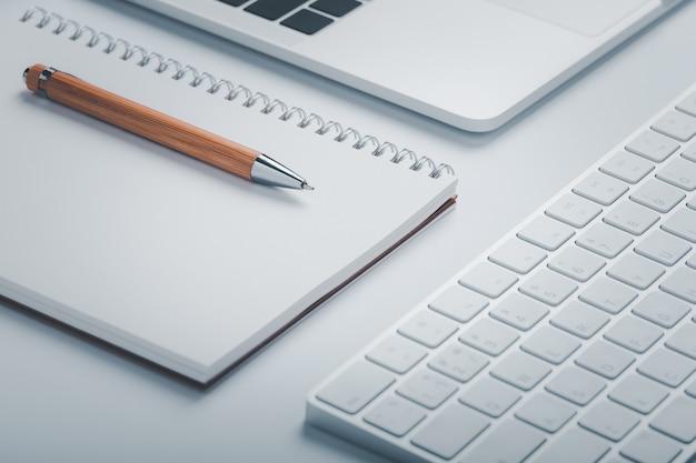 Strzał zbliżenie brązowy długopis z notatnikiem i klawiaturą w obszarze roboczym.