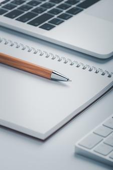 Strzał zbliżenie brązowy długopis z notebookiem i laptopem w obszarze roboczym.