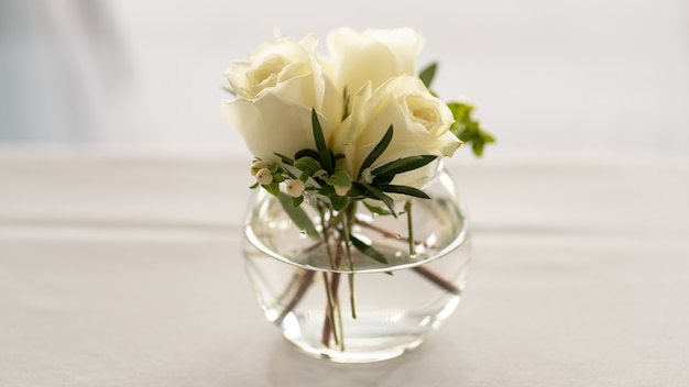 Strzał zbliżenie bukiet białej róży w szklanej misce na białym tle