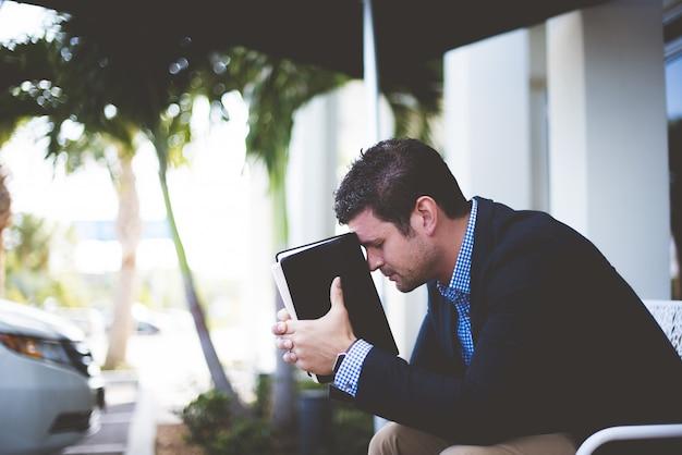 Strzał zbliżenie dobrze ubrany mężczyzna siedzi, trzymając biblię na głowie