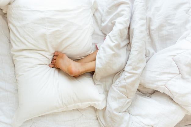 Strzał zbliżenie dziewczynka śpi do góry nogami i trzymając stopy na poduszce