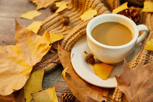 Strzał zbliżenie filiżankę kawy i jesienne liście na powierzchni drewnianych