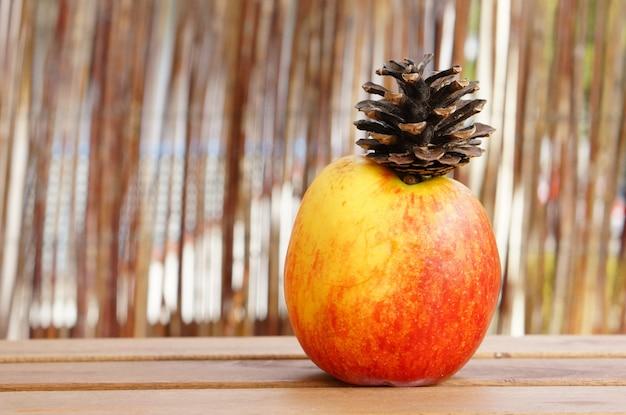 Strzał zbliżenie jabłka na stole z szyszką na górze