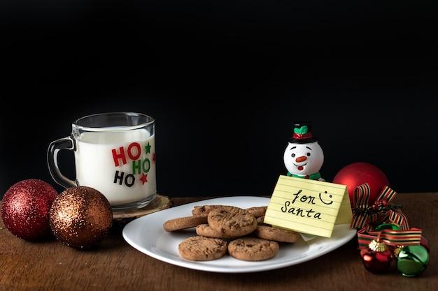 """Strzał zbliżenie karty """"dla świętego mikołaja"""" na smaczne ciasteczka, mleko i ozdoby świąteczne"""