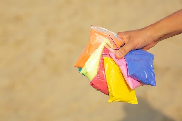Strzał zbliżenie kobiece ręki trzymającej torby suchej kolorowej farby holi na tle piasku. miejsce na tekst