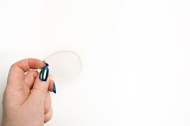 Strzał Zbliżenie Kobiecej Ręki Trzymającej Przezroczystą Gąbkę Silikonową Na Białym Tle. Miejsce Na Tekst Premium Zdjęcia
