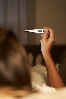 Strzał zbliżenie kobiety patrząc na termometr. kobiece ręce trzymając cyfrowy termometr. dziewczyna mierzy temperaturę.