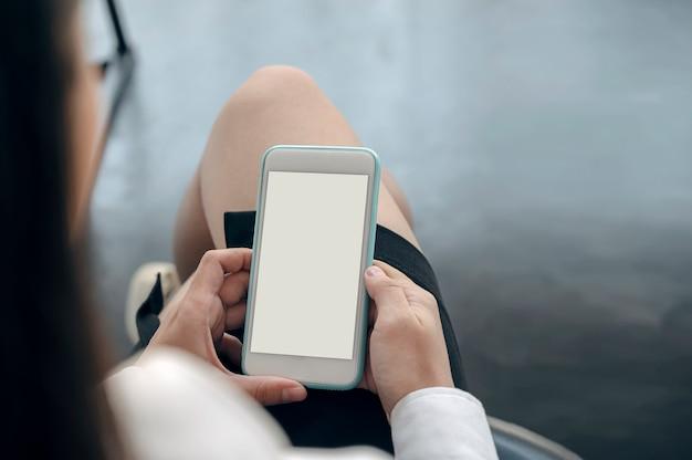 Strzał zbliżenie kobiety ręki trzymającej pusty ekran smartphone siedząc w biurze.