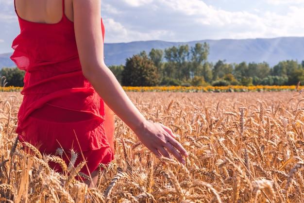 Strzał zbliżenie kobiety w czerwonej sukience w polu pszenicy w słoneczny dzień