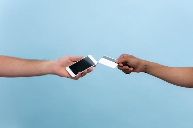 Strzał zbliżenie ludzi trzymając się za ręce na białym tle na niebieskiej ścianie. relacje, przyjaźń, partnerstwo, biznes lub rodzina. copyspace. trzymanie karty i smartfona. rachunek za płatności online.