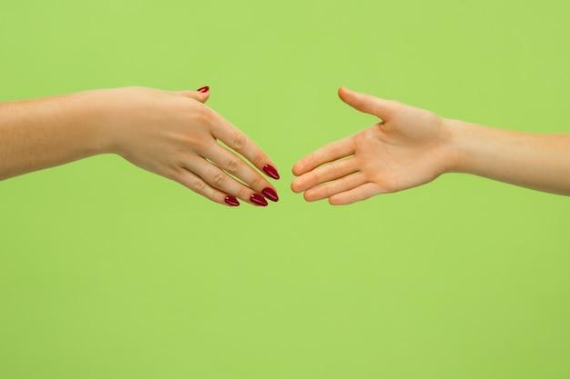 Strzał zbliżenie ludzi trzymając się za ręce na białym tle na zielono