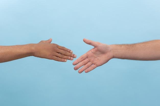 Strzał zbliżenie ludzi trzymając się za ręce na białym tle. pojęcie relacji międzyludzkich, przyjaźni, partnerstwa, biznesu lub rodziny.