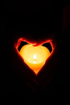 Strzał zbliżenie ludzkich rąk trzymających małą świeczkę