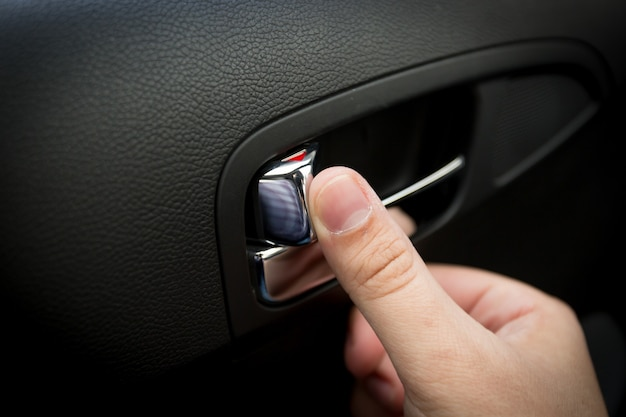 Strzał zbliżenie męskiego kierowcy naciskającego przycisk blokujący drzwi w samochodzie