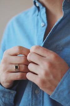 Strzał zbliżenie mężczyzny w formalnym stroju na sobie złoty pierścień
