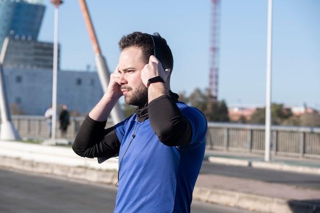 Strzał zbliżenie młodego mężczyzny słuchania muzyki przez słuchawki podczas joggingu na ulicy