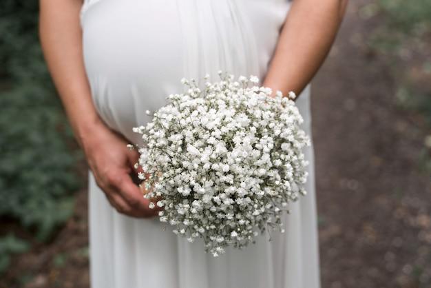 Strzał zbliżenie narzeczonej w ciąży z bukietem na jej ślub