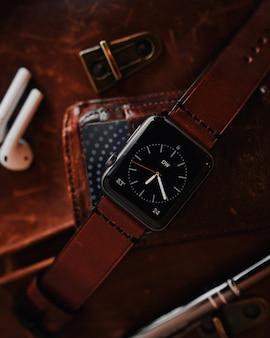 Strzał zbliżenie nowoczesnego chłodnego czarnego cyfrowego zegarka z brązowym skórzanym paskiem
