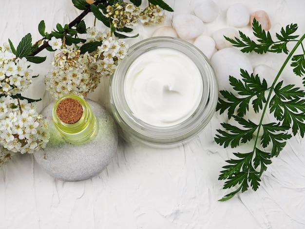Strzał zbliżenie organiczny olej i śmietana. zielona kompozycja kosmetyczna, świeże ziołowe kosmetyki do pielęgnacji skóry. olejek eteryczny, butelka rzemieślnicza, kwiaty, krem do twarzy w słoiku. naturalny środek pielęgnacyjny.