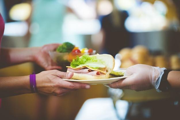 Strzał zbliżenie osoby obsługującej kanapkę na białym talerzu