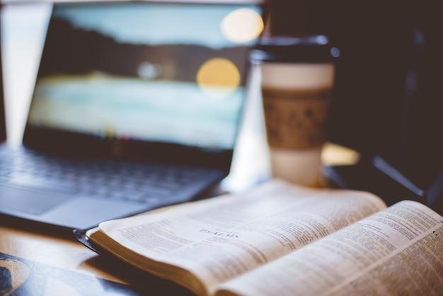Strzał zbliżenie otwartej biblii z niewyraźnym laptopem i kawą