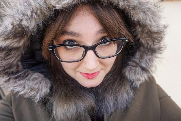 Strzał zbliżenie piękna dziewczyna w okularach, ubrany w płaszcz w zimowy dzień