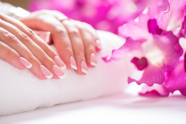 Strzał zbliżenie piękne kobiece dans z paznokciami francji manicure. koncepcja manicure i spa.
