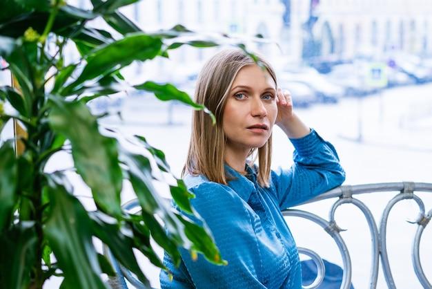 Strzał zbliżenie pięknej blondynki dojrzałej kobiety w niebieskiej sukience podczas relaksu przy oknie