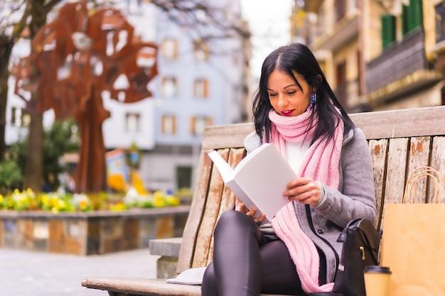 Strzał zbliżenie pięknej kaukaskiej kobiety siedzącej na ławce i czytającej książkę w publicznym parku
