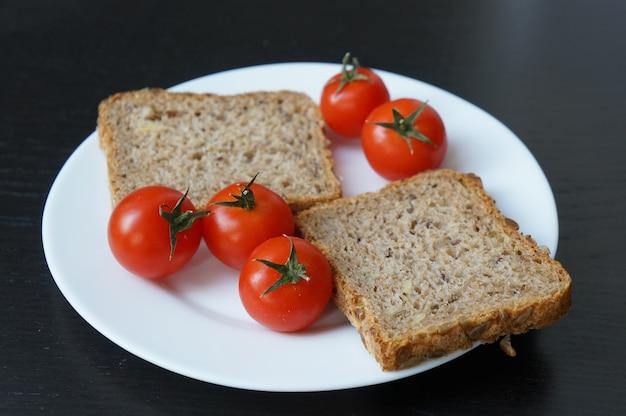 Strzał zbliżenie pomidory czereśniowe i kromka chleba na talerzu