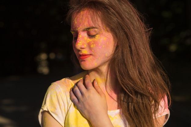 Strzał zbliżenie przepięknej brunetki pokrytej żółtą i różową farbą holi