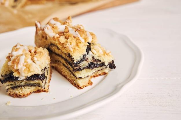 Strzał zbliżenie pyszne ziarna maku kawałki ciasta z białym polewą cukrową na białym stole