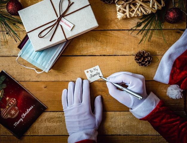 """Strzał zbliżenie ręce w białych rękawiczkach, pisząc """"do mojej rodziny"""" na karcie na prezent i maskę"""