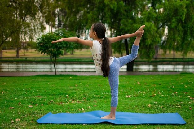 Strzał zbliżenie słodkie dziewczyny łacińskiej praktykujących jogę w parku