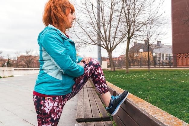Strzał zbliżenie sportowy rudowłosa kobieta robi ćwiczenia rozciągające na ławce w parku na świeżym powietrzu