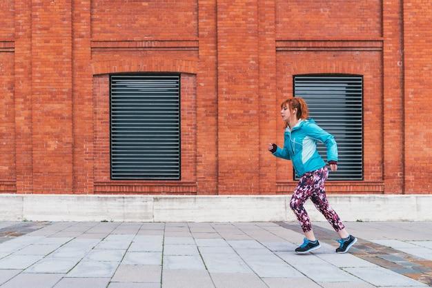 Strzał zbliżenie sportowy rudowłosej kobiety ćwiczeń na świeżym powietrzu