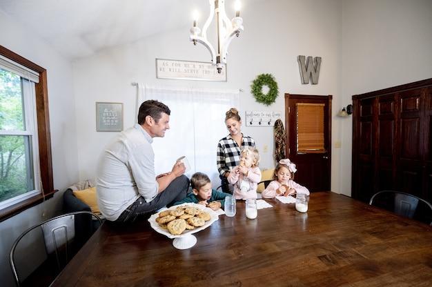 Strzał zbliżenie szczęśliwą rodzinę, jedzenie chipsów czekoladowych i mleka spożywczego - koncepcja rodziny