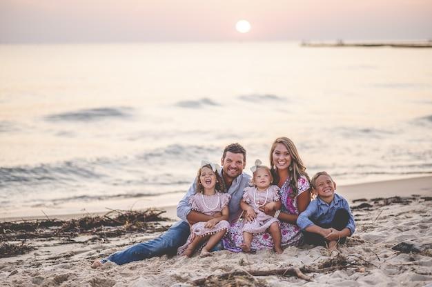 Strzał zbliżenie szczęśliwą rodzinę siedzi nad brzegiem morza o zachodzie słońca - koncepcja rodziny